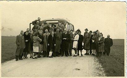 Ein Foto von Mitarbeitern und Mitarbeiterinnen  der Tötungsanstalt Hartheim  Sie stehen vor einem der Transport-Busse  während eines gemeinsamen Ausfluges.