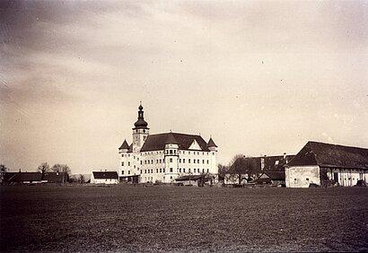 Ein Foto vom Schloss Hartheim, als es eine Tötungsanstalt war. Man sieht links vor dem Schloss die angeschlossene Bus-Garage.  Dort sind die Transport-Busse angekommen und die Opfer ausgestiegen.  Die Bus-Garage war an der West-Seite des Schlosses.